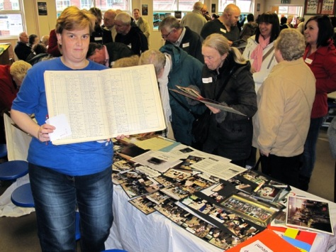 Parent and volunteer Rebecca Humpage shows visitors a school register for 1943-57