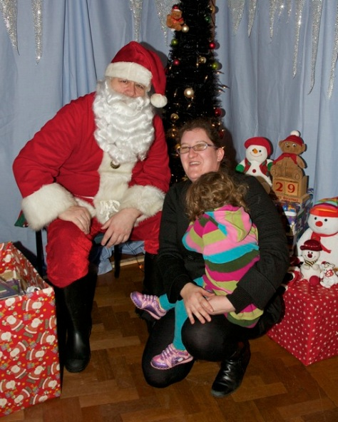 Santa gets up close and seasonal with mum Rebecca Rowley and daughter Connie, aged 2 1/2, in his grotto at Saint John's Christmas Fayre!
