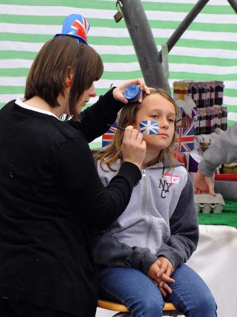A Union Flag takes shape on a youngster's face on Bloxwich Market