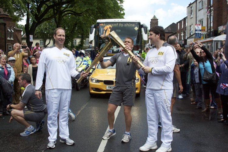 Giles Birt of Shrewsbury (left) passes the Olympic Flame to Thierry Laurent of Roswell, Atlanta, USA