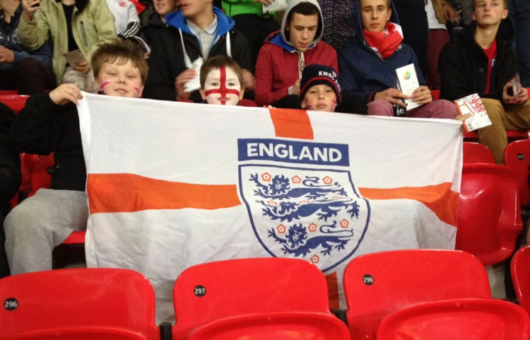 Jordan Hurst, Thomas Raybould and Tim Street of Leamore Primary School behind the England flag.