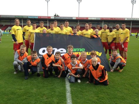 Leamore Primary School ball boys help out Walsall FC players.