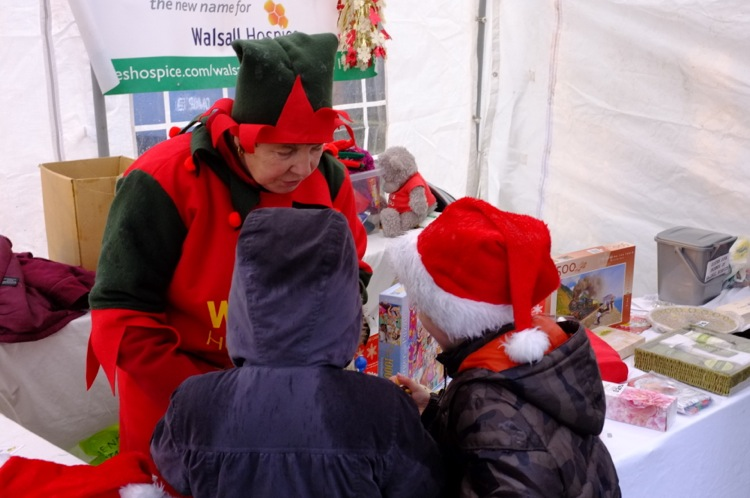 National Elf Pat Till of the Sister Dora Friends of Walsall Hospice engages youngsters in Christmassy conversation.