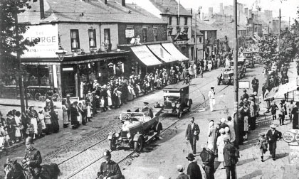 Bloxwich High Street, showing the georgian 'George' pub, shops and Bloxwich Carnival procession, 1920s