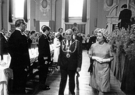 The Mayor of Walsall, Cllr Jim Leadbeater, shows the Queen to her seat in the Town Hall (pic Walsall Local History Centre)