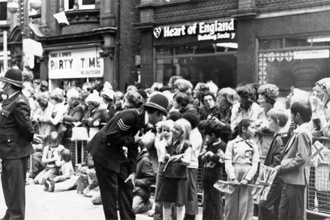 A friendly Walsall police sergeant shows his radio to curious children in Lichfield Street as the crowds wait