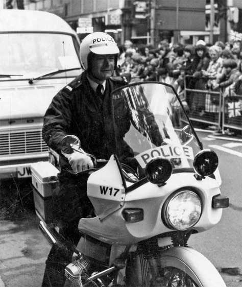 A police motorcyclist, part of the Royal escort